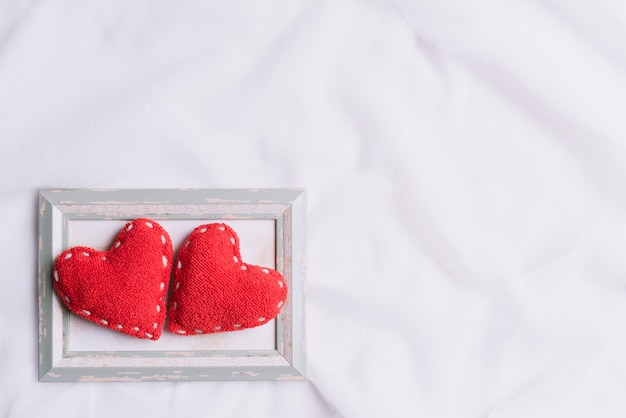 Two red hearts in picture frame on white fabric background.