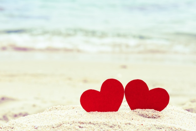 Two red hearts on the summer beach. love, wedding and valentines day concept