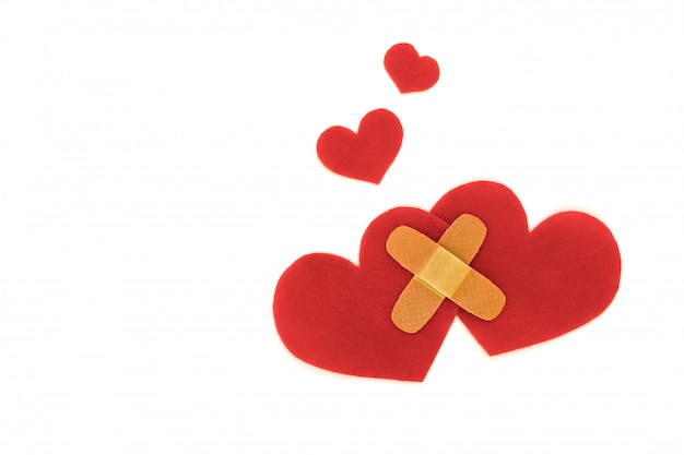 Two red hearts symbol with medical patch on white background