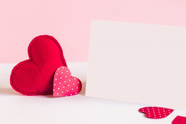 Two red hearts and a white sheet of paper