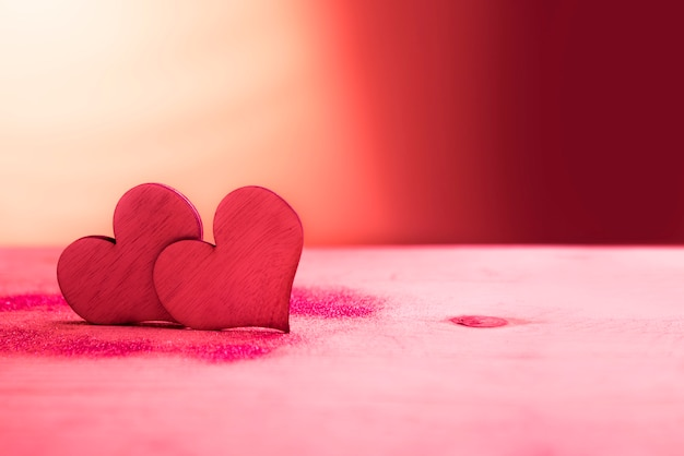 Two red hearts with glitter on pink table