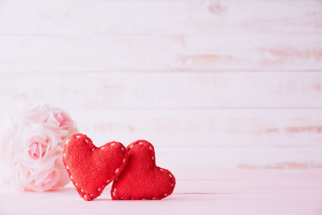 Two red hearts with pink rose flower on wooden background.