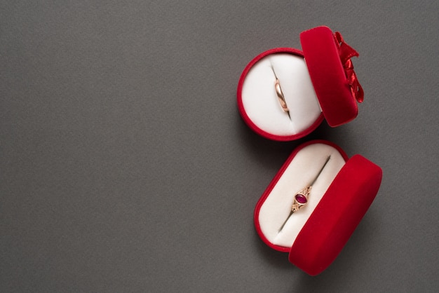 Two red jewelry boxes with jewelry on a black background. top view. copy space