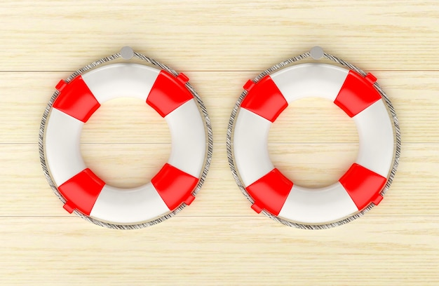 Two red lifebuoys hanging on a wooden wall.