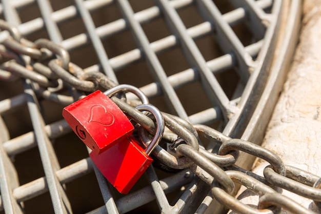 체인에 두 개의 빨간 사랑 자물쇠를 닫습니다.