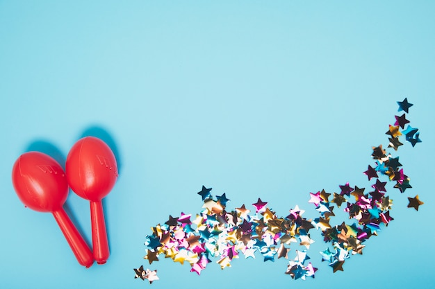 Two red maracas with colorful star shape confetti against blue backdrop