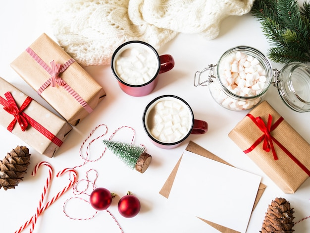 Two red mugs with hot drink and marshmallows, paper card for letter, envelope and xmas decoration. flat lay for merry christmas or happy new year. top view. copy space
