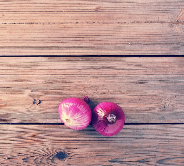 Two red onions on rustic wooden background