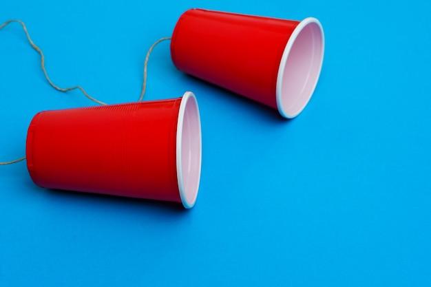 青いおもちゃの電話のロープで接続された2つの赤い紙カップ