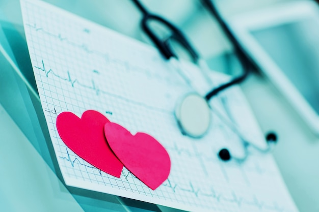 Two red paper heart on the electrocardiogram the cardiologist