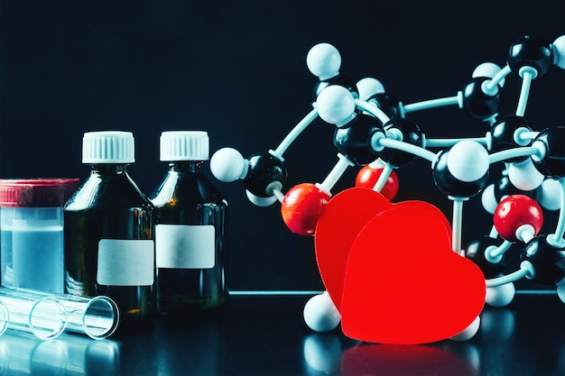Two red paper hearts and molecular structure model