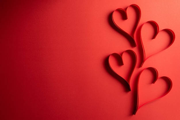 Two red paper hearts on red