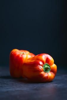 Два красных перца на черной поверхности