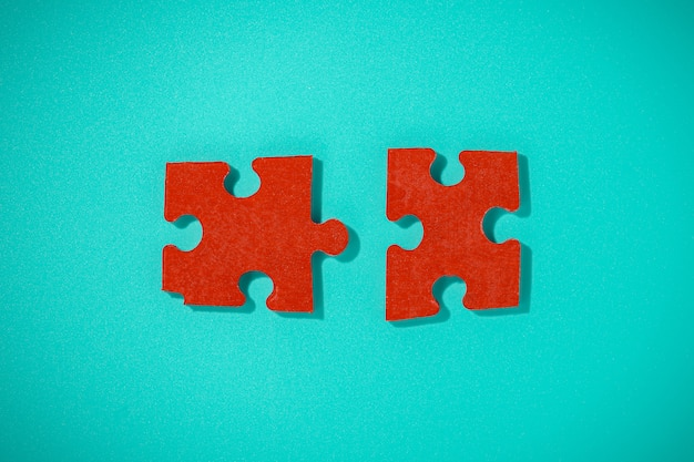 Two red piece flat puzzle jigsaw on blue table