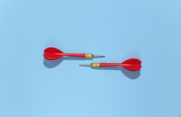 Два красных пластиковых дротика с металлическим наконечником на синем ярком фоне с глубокой тенью.