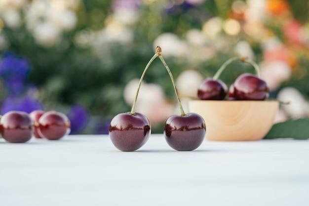 甘いサクランボのボウルの横にある花の茂みの背景にある木製のテーブルの上に立っている2つの赤い熟したサクランボの果実