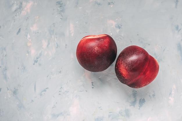 Два красных спелых плода нектарина крупным планом