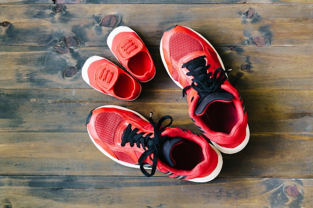 Two red sport running shoes or sneakers of mother or father and child on wood
