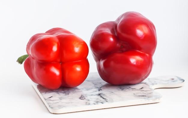 Два красных сладких перца, трех- и четырехкамерные на доске мраморного цвета.