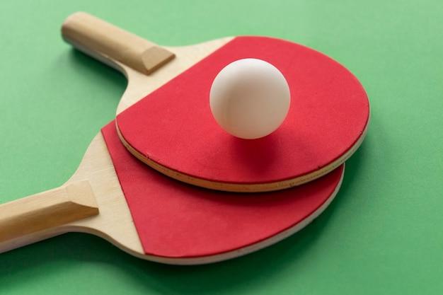 白いボールと2つの赤いテニスラケットがテーブルの上にあります