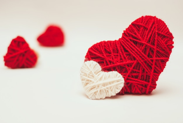 Two red and white clews in shape of heart made from yarn