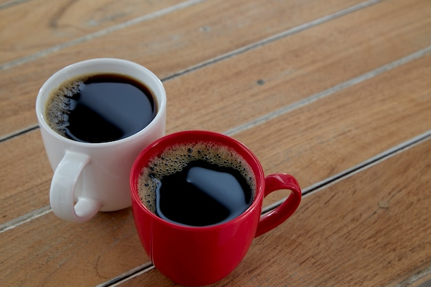Two red and white mug coffee on wooden