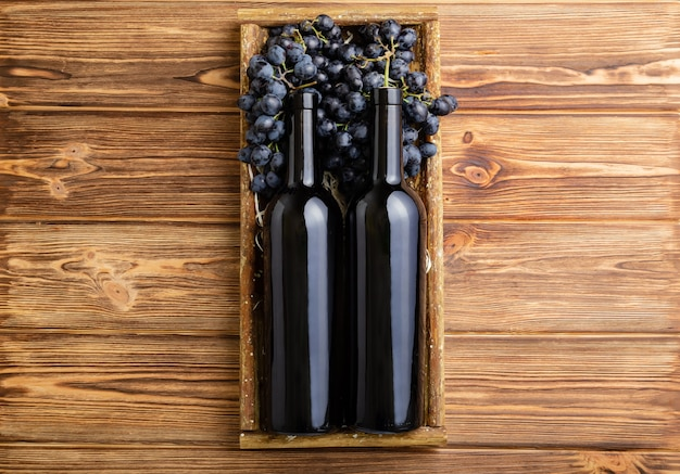 Two red wine bottles composition on brown wooden table. red wine bottles in box on black ripe grapes on wooden table. old collection wine label template top view.