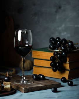 Two red wine glass and cheese platter on rustic top view