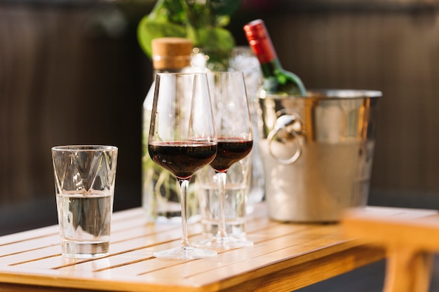 Two red wine glasses and glass of water on wooden table
