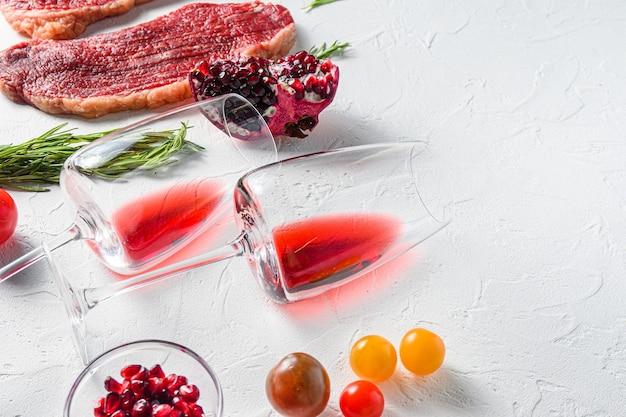 조미료와 쇠고기 스테이크를 곁들인 두 개의 레드 와인 잔