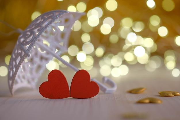 Два красных деревянных сердца под зонтиком