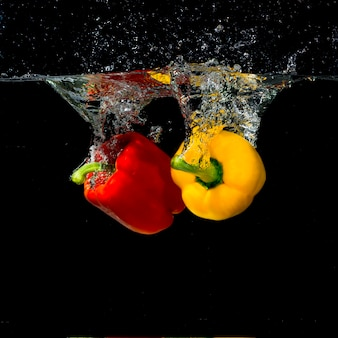 Two red and yellow bell pepper splashes into water