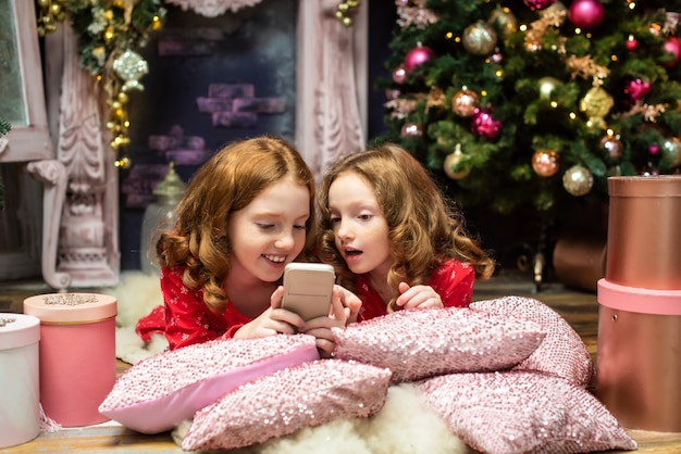 Две рыжеволосые сестры возле новогодних елок, глядя на телефон рождество