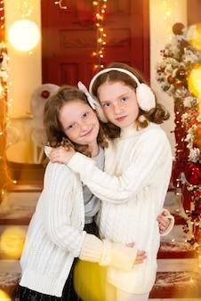 Две рыжие сестры на веранде дома, украшенного к рождеству