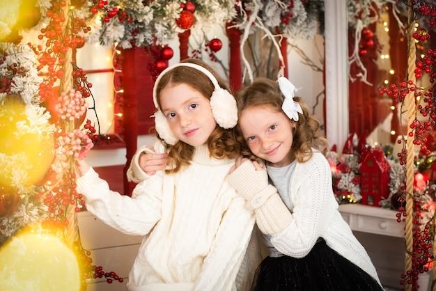 クリスマスに飾られた家のベランダにいる2人の赤毛の姉妹