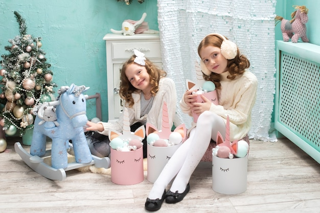Two redhaired sisters on the veranda of a house decorated for christmas