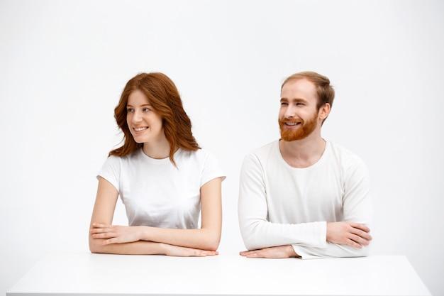 赤毛の大人2人がテーブルに座って、笑顔で左を見る