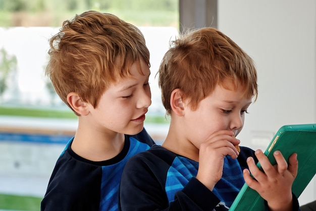 Two redhead brothers playing games on  tablet