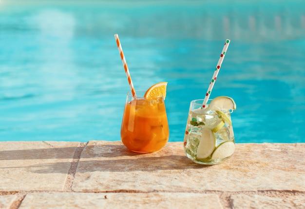 Два освежающих коктейля возле бассейна крупным планом