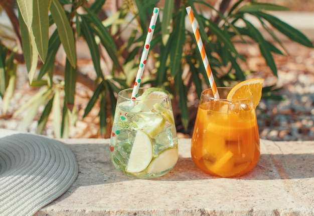Two refreshing cocktails near a garden plants and straw hat close up