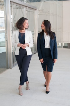Two relaxed female colleagues walking in office hall