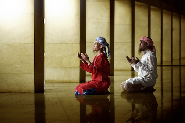 Two religious muslim man praying together