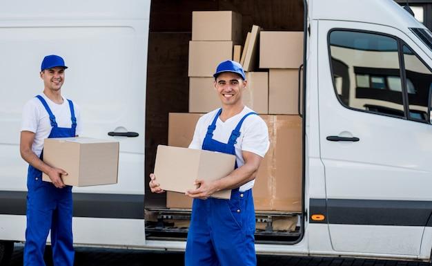 Двое работников транспортной компании выгружают ящики из микроавтобуса в новый дом