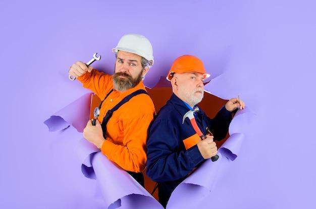 Два ремонтника работают с инструментами для ремонта через бумажного строителя в рекламе строительного шлема