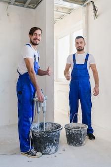 青いオーバーオールの2人の修理工がバケツでセメントを準備します