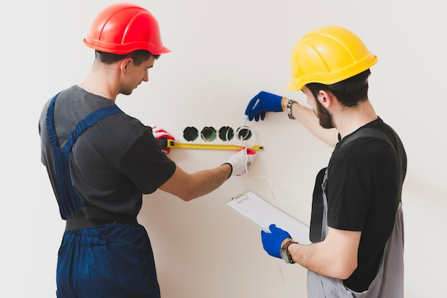 Two repairmen making measures at wall