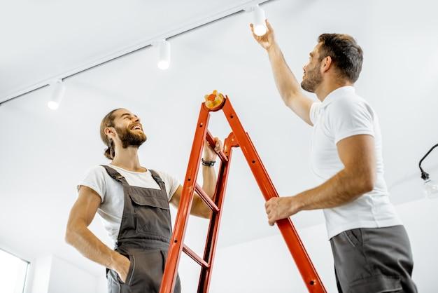 モダンなアパートのリビングルームのはしごの上に立って、光点を設置する2人の修理工または専門の電気技師
