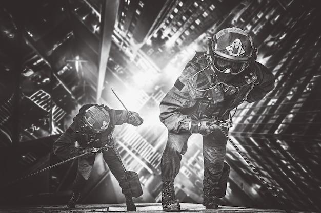 Двое спасателей спускаются с небоскреба, чтобы спасти людей от пожара. понятие о катаклизмах, трагедиях, пожарах. смешанная техника