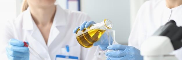 Two researchers in laboratory examine golden liquid in test tube laboratory diagnostics concept