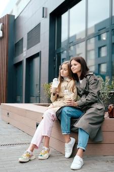モダンな建物のそばに座ってレジャーを楽しみながら飲み物を持つスマートカジュアルの2つの安らかな女性